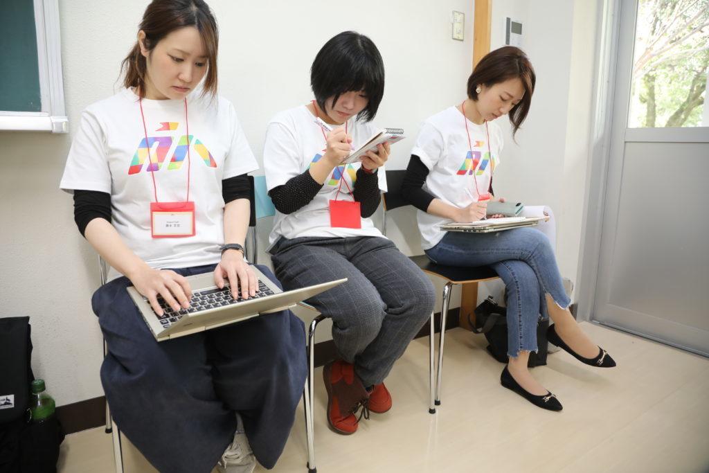写真:当日スタッフの女性3人が、セッションのメモをとっている