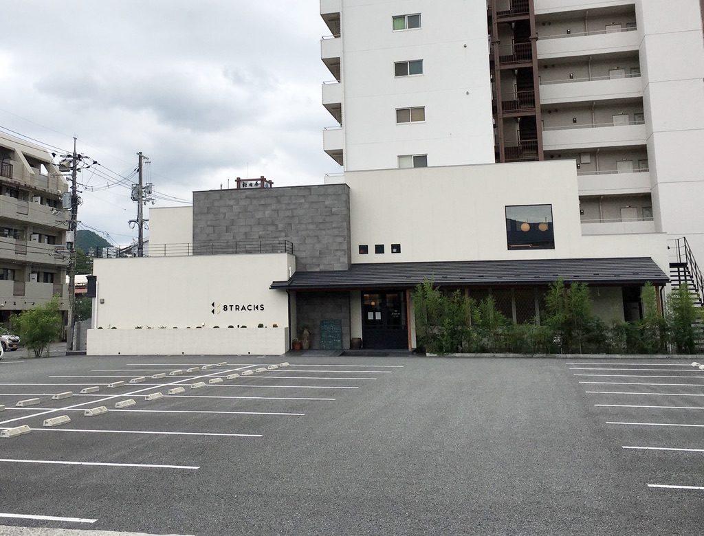 写真:懇親会一次会会場の外観。手前に広い駐車場がある。建物には「8TRACKS」と書かれている。