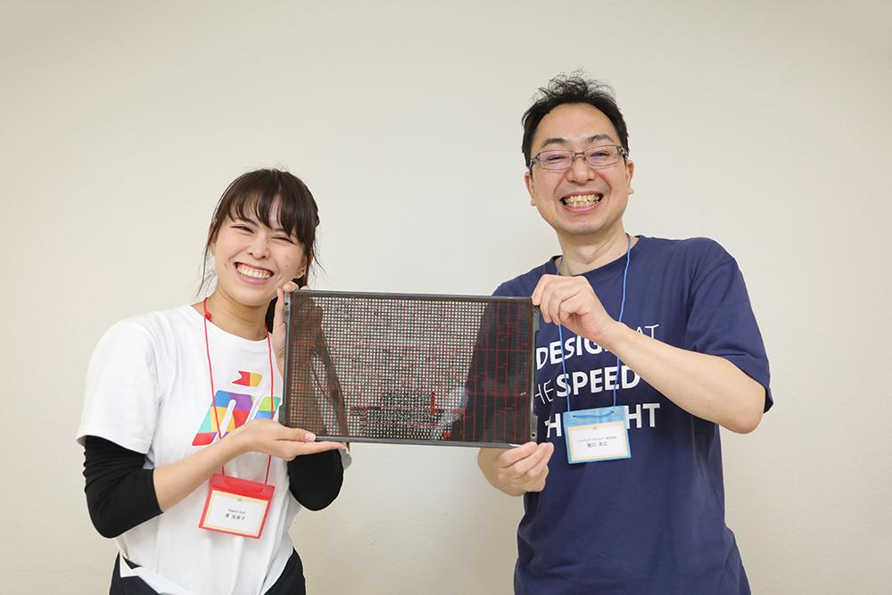 写真:関口浩之さん(右)とスタッフの東さん(右)写植の板を持って。