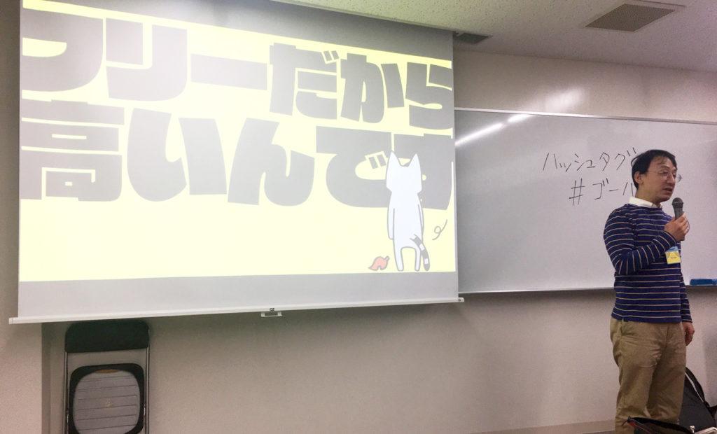 写真:「フリーだから高いんです」と書かれたスライドを背に話す深沢さん