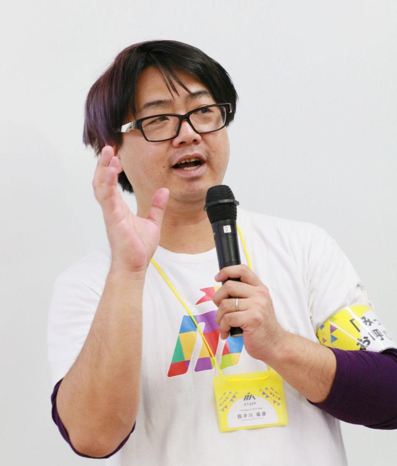 写真:茄子川導彦さんが講演する様子。笑顔で左手にマイクを持ち、右手を上げている