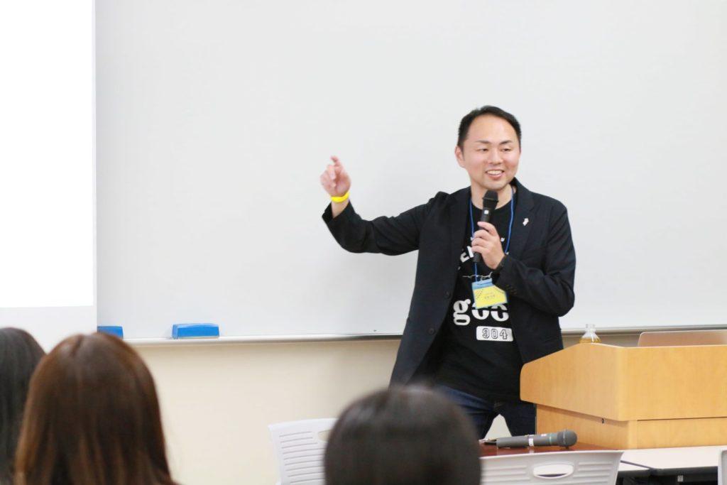 写真:右手を挙げて話す吉田さん。