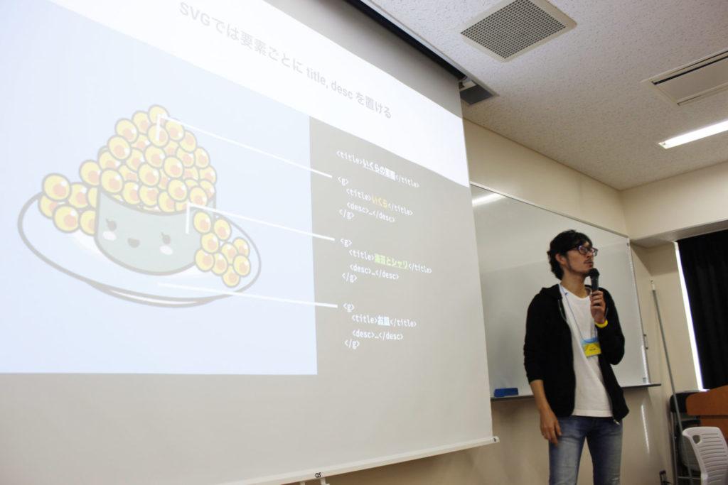 写真:松田さん。いくらの軍艦巻きの可愛いイラストを例に、SVGに文字データを含められるということを説明中。