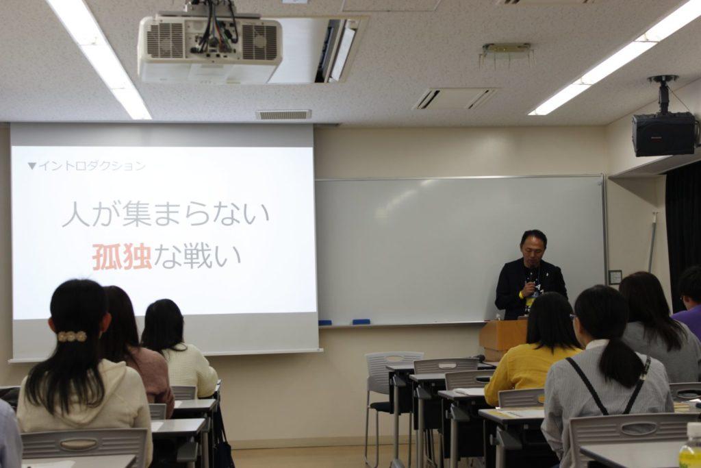 写真:「人が集まらない孤独な戦い」というスライドを表示しお話しする吉田さん。