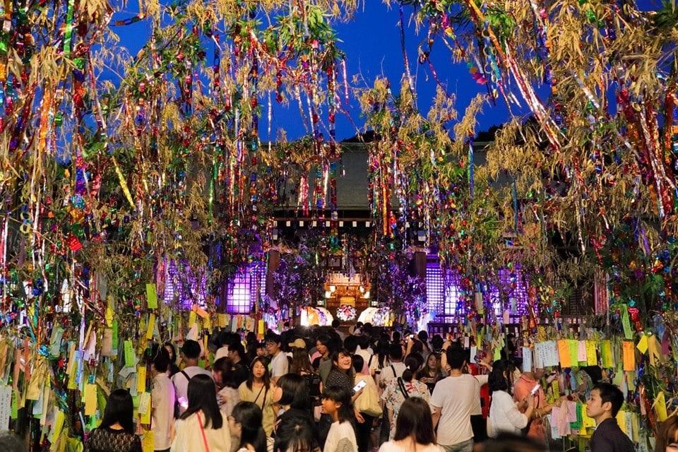 写真:七夕祭りに集まる大勢の人々。大きな笹の木にたくさんの短冊、ライトアップなど、華やかな様子が伝わってくる。